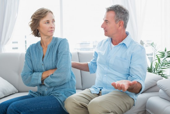 Middle aged couple sitting on the sofa having a dispute at home