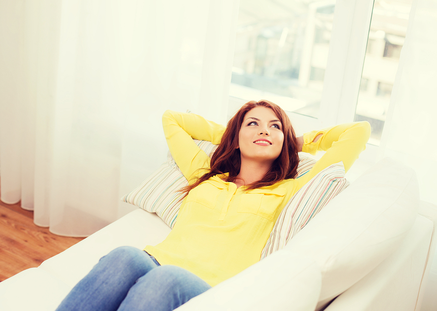 home and happiness concept - smiling young woman lying on sofa a