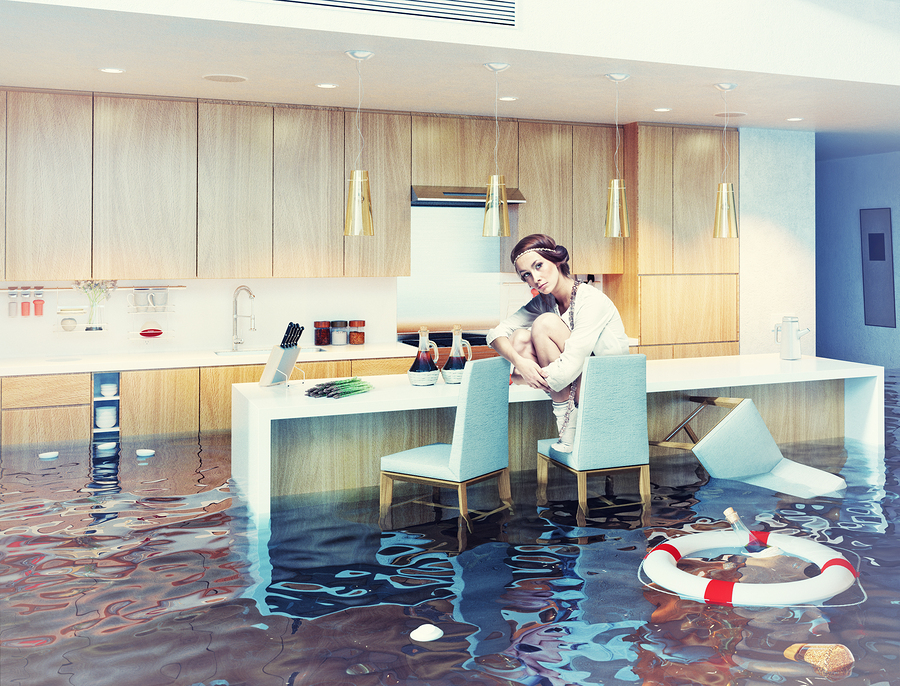 beautiful woman sitting on a chair in flooded kitchen interior.
